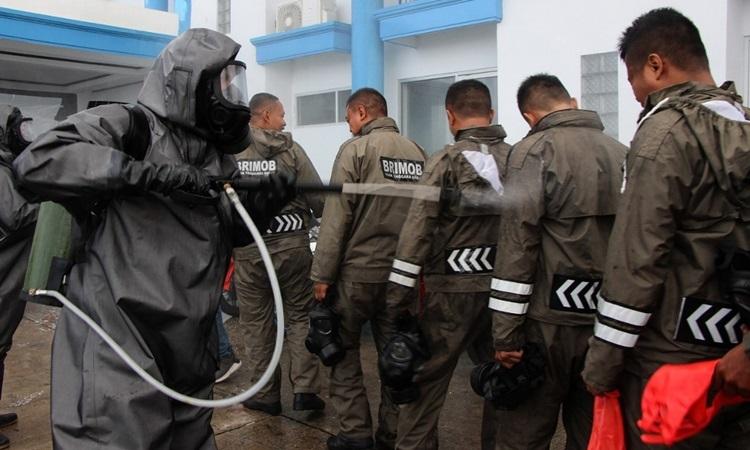 Cảnh sát Indonesia phun khử trùng cho nhau trước khi thực hiện các biện pháp khử trùng tại khu du lịch trên đảo Lombock hôm 18/3. Ảnh: AFP.