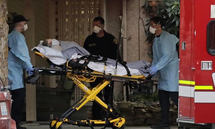 Nhân viên y tế di chuyển người nhiễm nCoV ở New York lên xe cứu thương. Ảnh: ABC.
