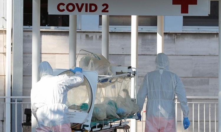 Nhân viên y tế di chuyển một bệnh nhân nhiễm nCoV trên cáng cách ly tại phòng khám Columbus ở Rome, Italy, ngày 16/3. Ảnh: Reuters.
