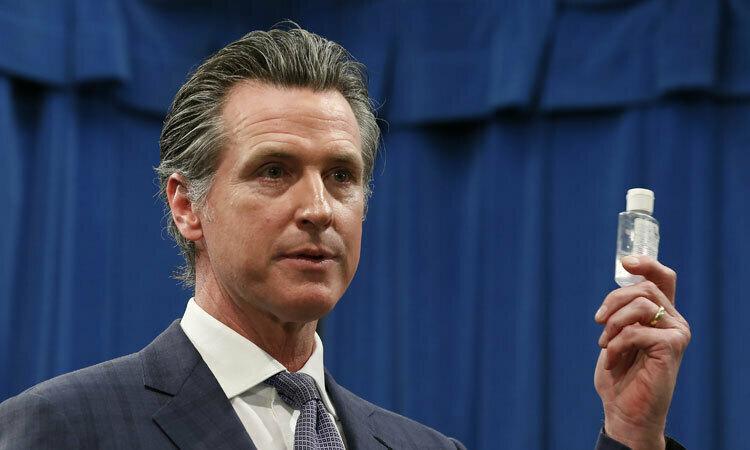 Thống đốc Gavin Newsom cầm chai nước rửa tay khi phát biểu tại họp báo ở California hôm 4/3. Ảnh: AP.