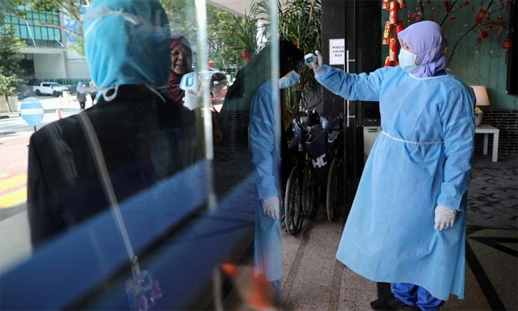 Y tá đo thân nhiệt để phát hiện người có triệu chứng nhiễm nCoV tại một bệnh viện tại thủ đô Kuala Lumpur, Malaysia ngày 3/2. Ảnh: Reuters.