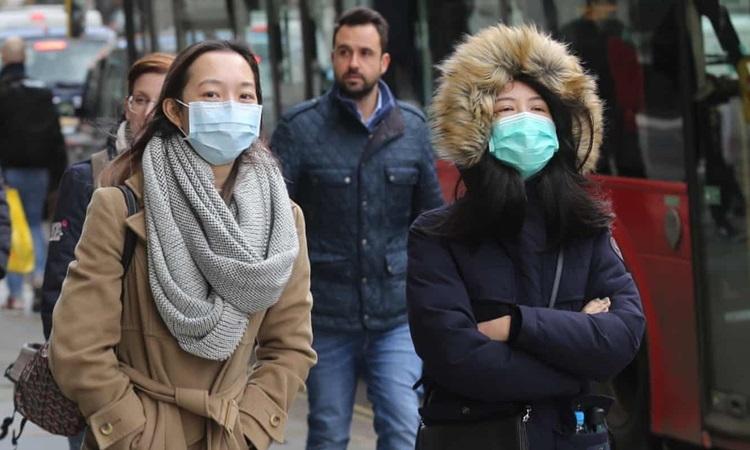 Người dân Anh đeo khẩu trang phòng dịch trên đường phố London hồi cuối tháng 2. Ảnh: Anadolu.