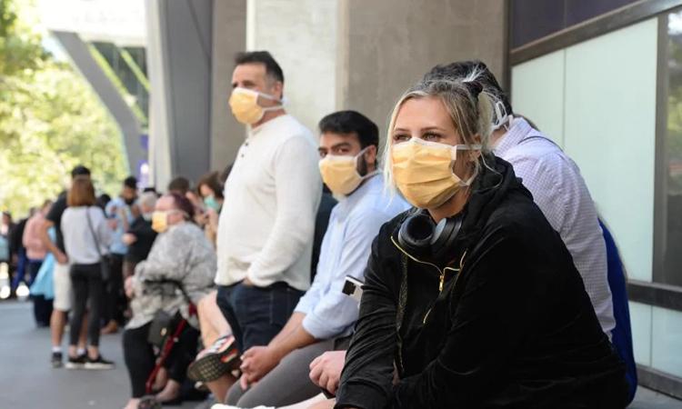 Người dân Australia ngồi chờ xét nghiệm nCoV bên ngoài Bệnh viện Hoàng gia Melbourne hôm 10/3. Ảnh: Herald Sun.