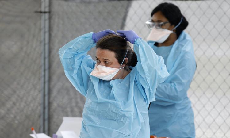 Nhân viên y tế buộc lại khẩu trang tại Bệnh viện Roper St. Francis, ở Nam Carolina hôm 16/3. Ảnh: AP.