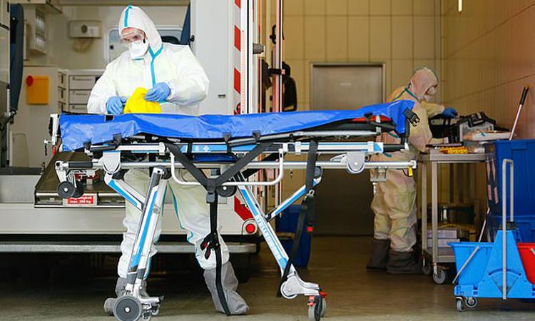 Nhân viên y tếkhử trùng cáng cứu thương tạimột bệnh viện ở Cologne. Ảnh: Reuters.
