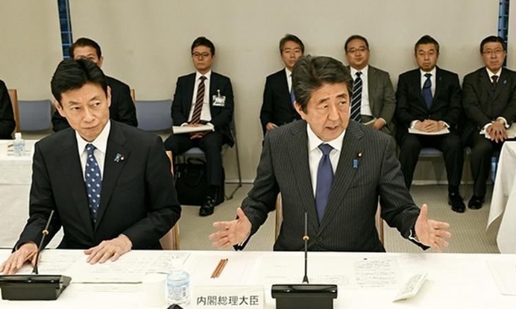 Thủ tướng Nhật Bản Shinzo Abe (phải) trong cuộc họp về Covid-19ở Tokyo hôm nay. Ảnh: AFP.