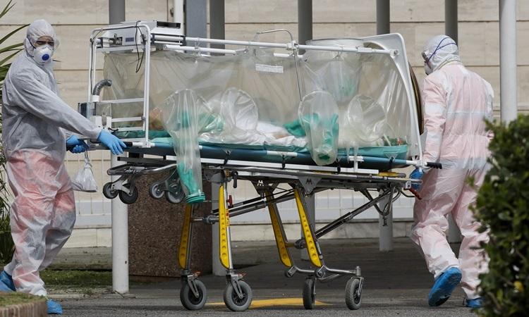 Nhân viên y tế đưa bệnh nhân nhiễm nCoV từ xe cứu thương lên cáng tại Bệnh viện  Columbus Covid 2 ở Rome hôm 19/3. Ảnh: AP.