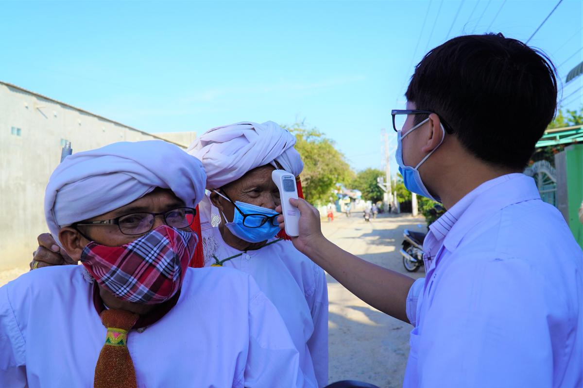 Nhân viên y tế đothân nhiệt chongười Chăm ở thôn xã Phước Nam, chiều 19/3. Ảnh: Việt Quốc.