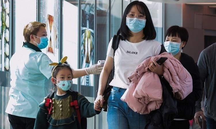 Nhân viên y tế kiểm tra thân nhiệt hành khách tại sân bay quốc tế Changi, Singapore, hồi cuối tháng hai. Ảnh: AFP.