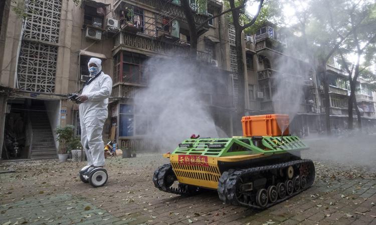 Tình nguyện viên điều khiển xe phun hóa chất khử trùng tại một khu dân cư ở Vũ Hán, Trung Quốc ngày 16/3. Ảnh: AFP.