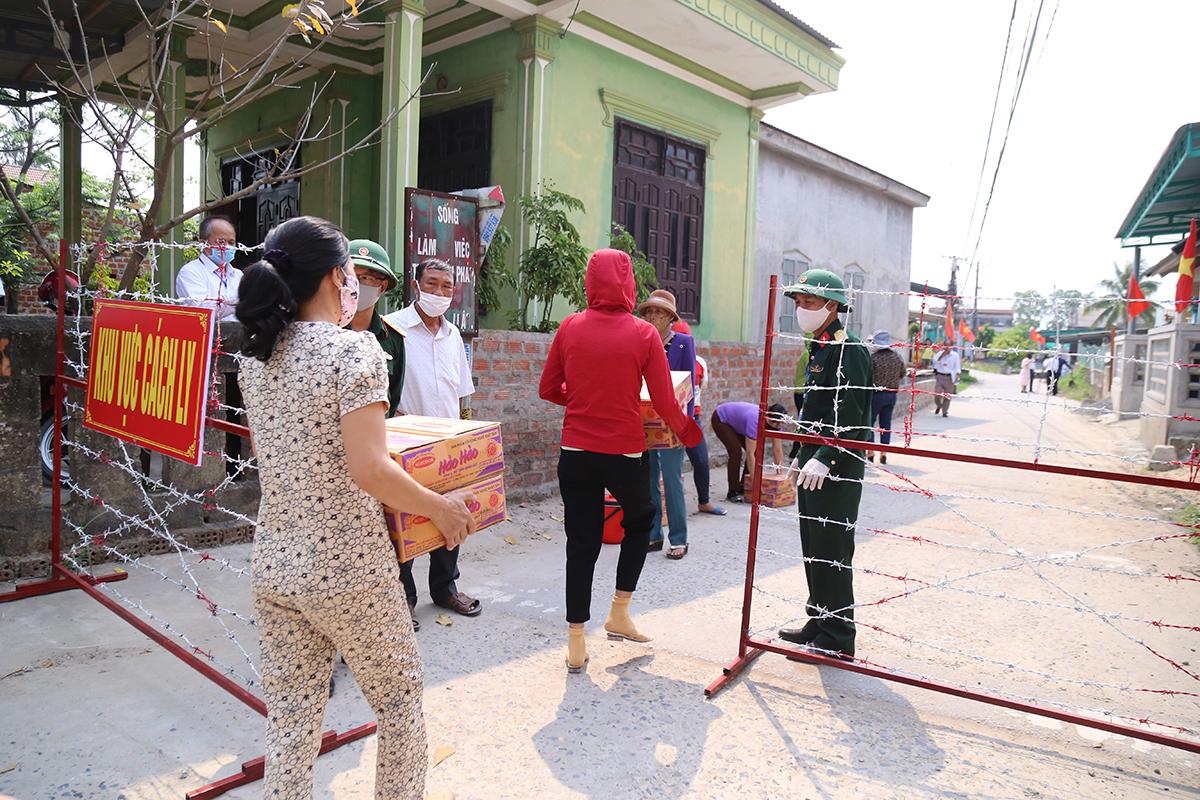 Người dân nhận lương thực trong diễn tập phong toả thị trấn vùng biển. Ảnh: Hoàng Táo