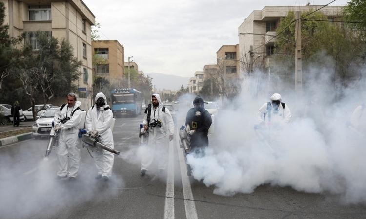 Lính cứu hỏa phun khử trùng đường phố Iran ngày 20/3. Ảnh: Reuters.