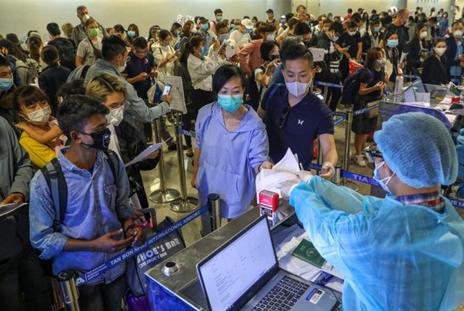 Nhiều hành khách đến sân bay Tân Sơn Nhất đã đeo khẩu trang. Ảnh: Hữu Khoa.