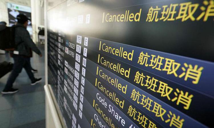 Hành khách đi qua bảng lịch trình các chuyến bay bị hủy do Covid-19 tại sân bay quốc tế Haneda ở Tokyo, Nhật Bản hôm 18/3. Ảnh: AP.
