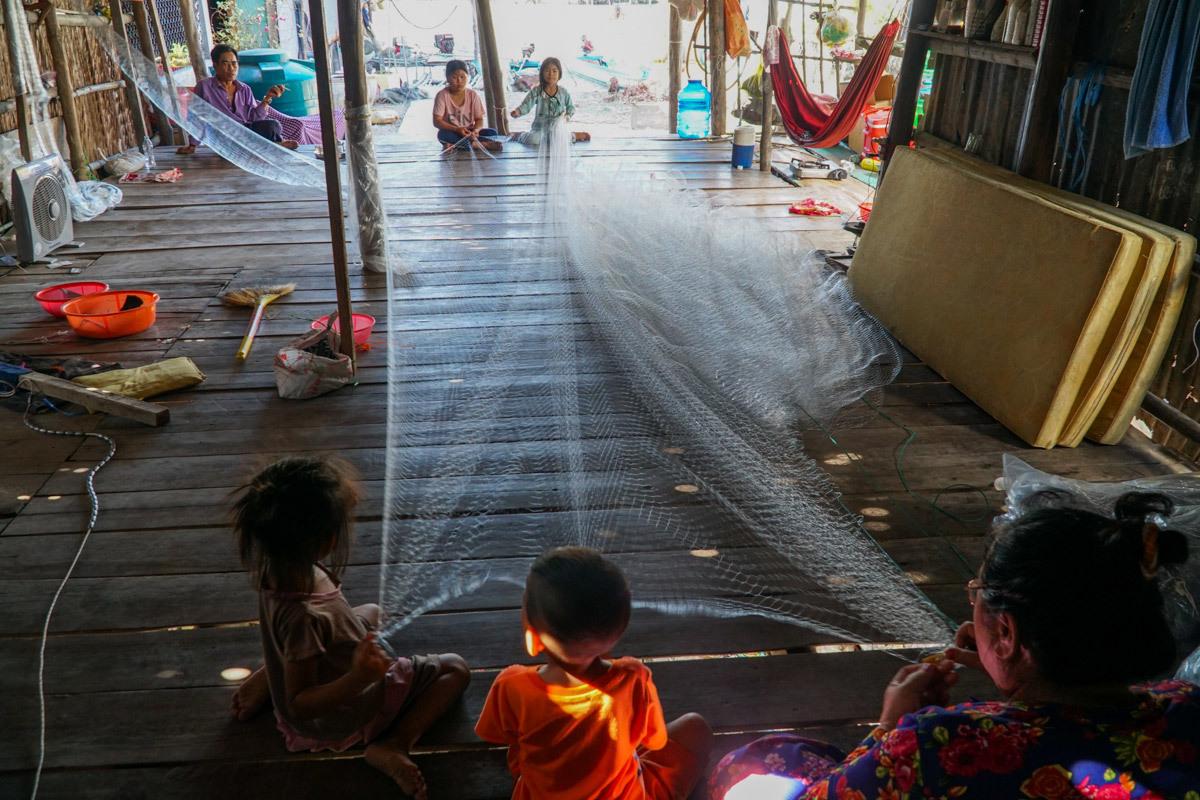 Cả nhà ông Ba Lý đan lưới để mưu sinh trong ngôi nhà không cửa. Ảnh: Phạm Linh.