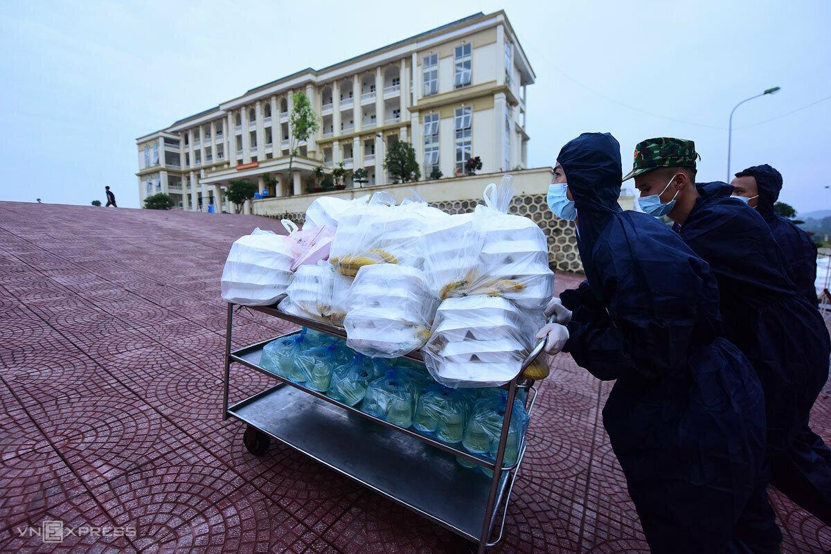 Bộ đội phục vụ trong khu cách ly đưa cơm chiều 20/3 tại Trường quân sự Bộ Tư lệnh thủ đô. Ảnh: Giang Huy.