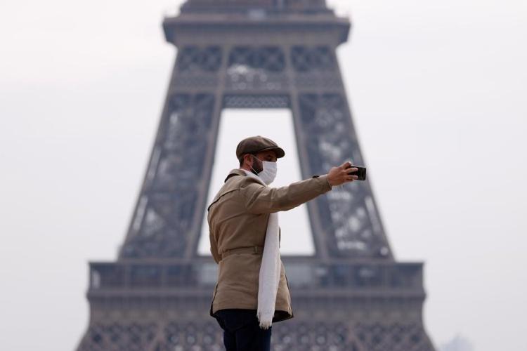 Một người mang khẩu trang chụp ảnh trước tháp Eiffel, Paris, Pháp, ngày 17/3. Ảnh: Reuters.