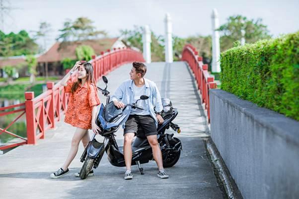 Xe điện Anbico Jeek bên cạnh hai bạn trẻ.
