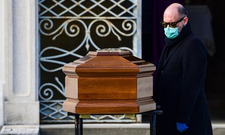 Người đàn ông đeo khẩu trang đứng cạnh quan tài mẹ chết vì nhiễm nCoV trong lễ tang gần phốBergamo, Lombardy hôm 20/3. Ảnh: AFP.