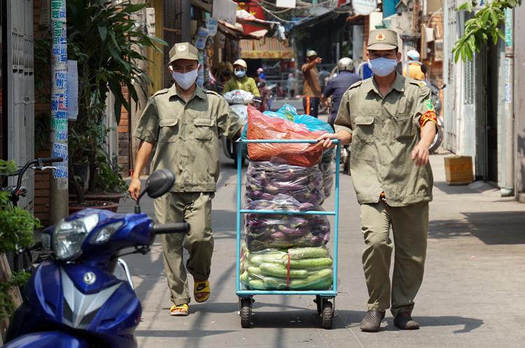 Dân phòng đưa thực phẩmvào cho các hộ dân bị cách ly ở phường 1, quận 8 sáng 23/3. Ảnh: Mạnh Tùng
