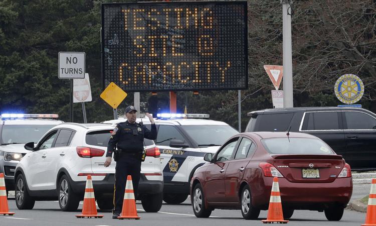 Nhân viên an ninh điều hướng xe vào điểm xét nghiệm Covid-19 tạiParamus, bang New Jersey hôm 20/3. Ảnh: AP.