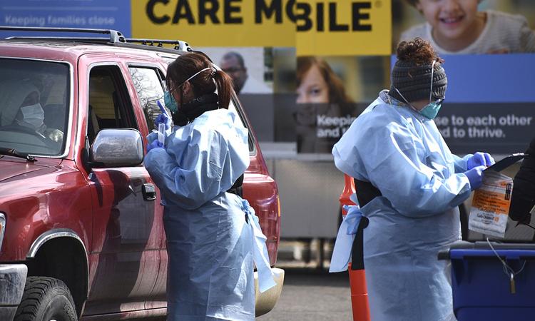 Hai nhân viên y tế chuẩn bị lấy mẫu xét nghiệm cho tài xế ởBillings, bang Montana hôm 20/3. Ảnh: AP.
