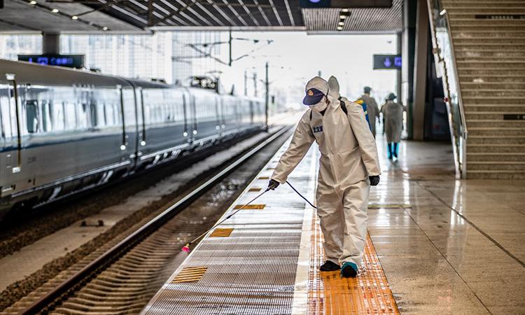 Nhân viên phun hóa chất tẩy trùng tại ga Vũ Hán ngày 24/3. Ảnh: AFP.