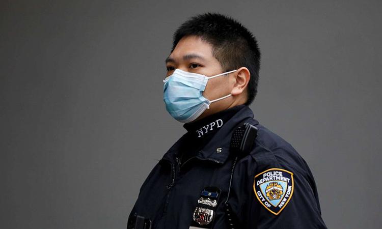 Một sĩ quan Sở cảnh sát thành phố New York (NYPD) đeo khẩu trang tại quận Manhattan, New York, Mỹ hôm 20/3. Ảnh: Reuters.