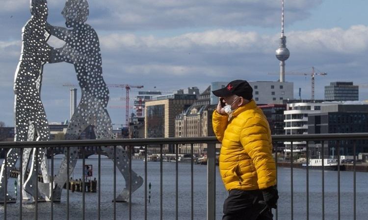 Người đàn ông đeo khẩu trang trên đường phố Berlin, Đức hôm 21/3. Ảnh:AFP.