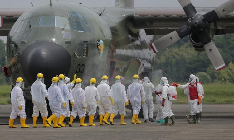 Binh sĩ Indonesia chuẩn bị chuyển thiết bị y tế tại sân bay Jakarta hôm 23/3. Ảnh: AFP.