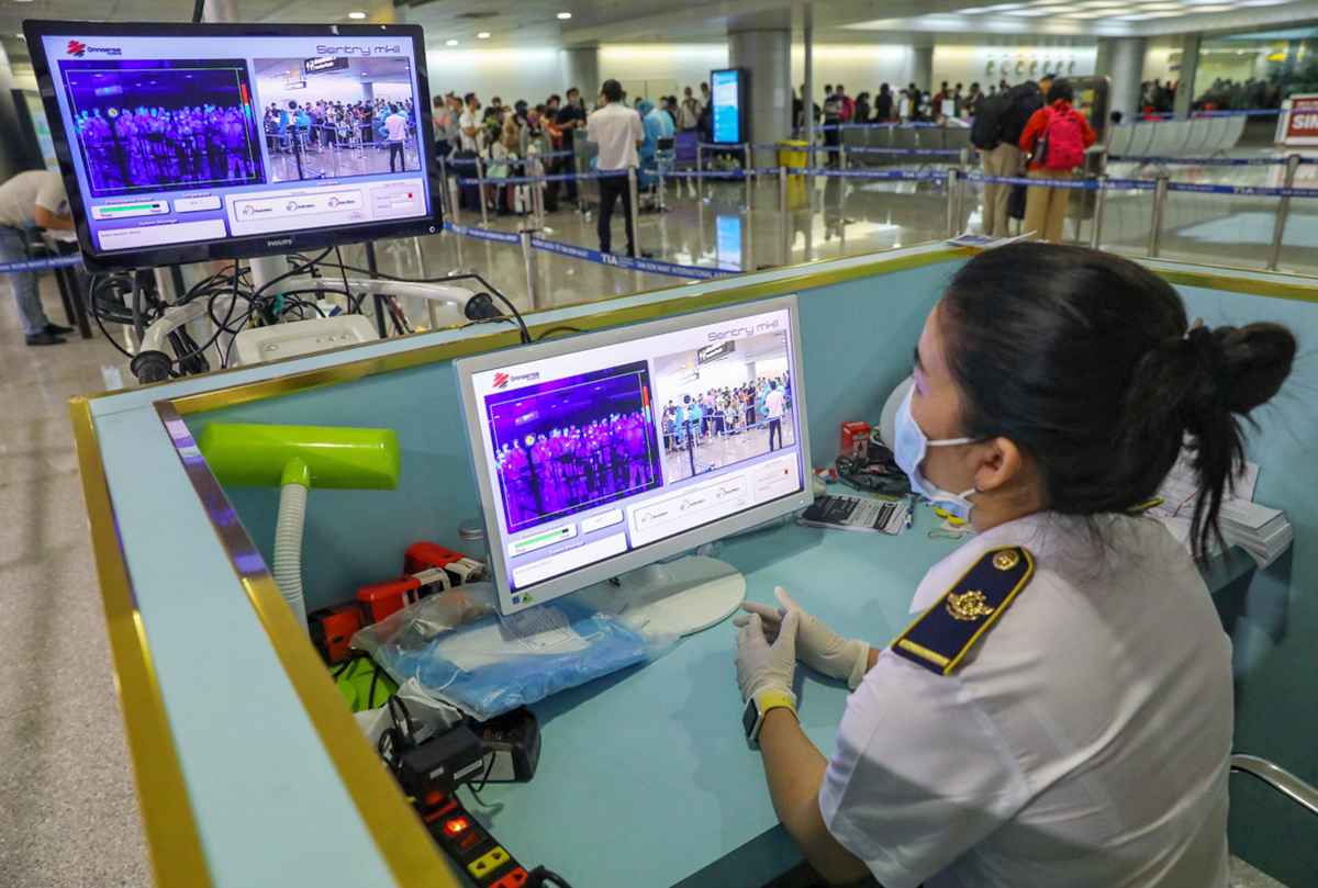 Nhân viên Trung tâm Kiểm dịch Y tế Quốc tế TP HCM (Sở Y tế) giám sát thân nhiệt người nhập cảnh tại sân bay Tân Sơn Nhất. Ảnh: Hữu Khoa.