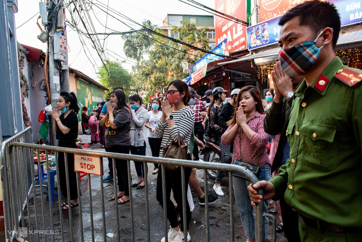 Sau khi nhà chức trách lập hàng rào trước cổng phủ Tây Hồ, nhiều người dân vẫn đứng ngoài làm lễ vọng vào trong. Ảnh: Thanh Huế
