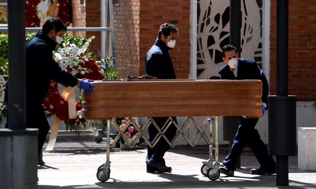 Nhân viên nhà tang lễ tại nghĩa trang La Almudena ở Madrid ngày 24/3. Ảnh: AFP.