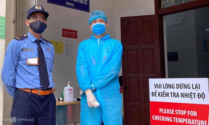 Nhân viên y tế trực kiểm tra nhiệt độ cho người đến khám tại Bệnh viện Bạch Mai. Ảnh:Đỗ Hằng