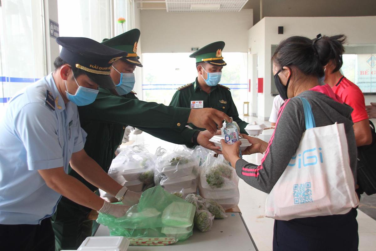 Nhà chức trách cửa khẩu quốc tế Lao Bảo phát cơm cho người nhập cảnh trong lúc chờ đưa đi cách ly tập trung. Ảnh: Hoàng Táo