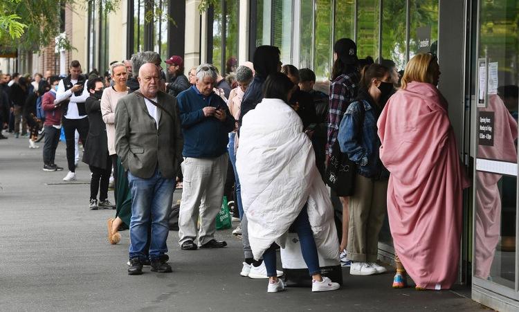 Người dân xếp hàng ngoài trung tâm phúc lợi xã hội ở Melbourne hôm 23/3. Ảnh: AFP.