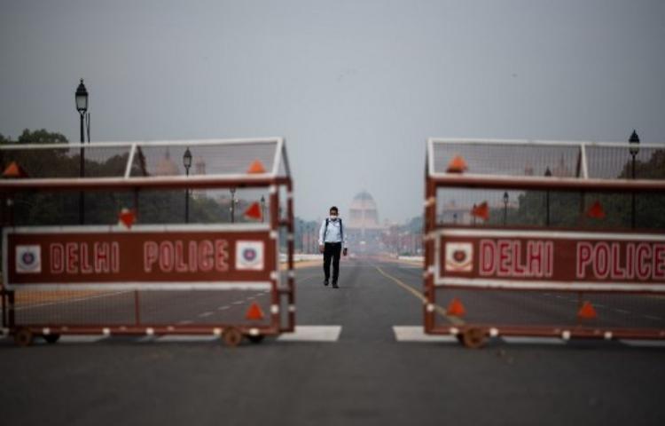 Người đàn ông Ấn Độ đi trên một con đường vắng tanh ở New Delhi hôm 24/3. Ảnh: AFP.