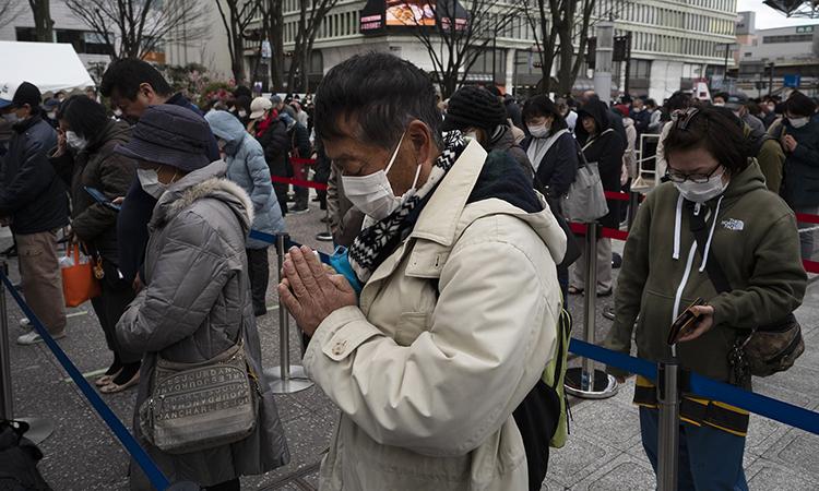 Nhiều người cầu nguyện khi theo dõi buổi lễ rước đuốc Olympic ở thành phố Fukushima hôm 24/3. Ảnh: AP.