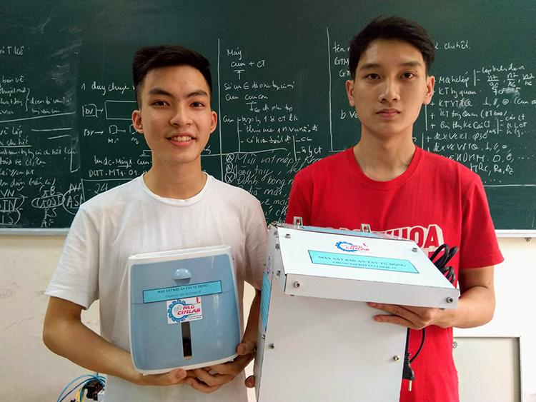 Sinh viên Dương Thế Long (trái) và Lưu Văn Thạo (phải) cùng hai phiên bản của máy rửa tay tự động. Ảnh: NX.