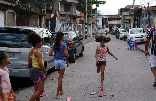 Trẻ em chơi đùa tại khu ổ chuột Cidade de Deus, phía tâyRio de Janeiro hôm 22/3. Ảnh: Reuters