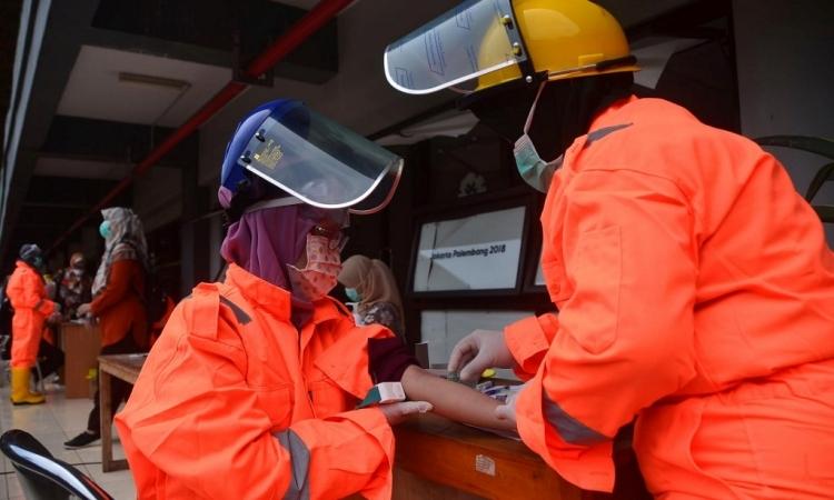 Nhân viên y tế Indonesia hỗ trợ xét nghiệm nCoV hàng loạt tại sân vận động Patriot ở Bekasi, Tây Java hôm 25/3. Ảnh: AFP.