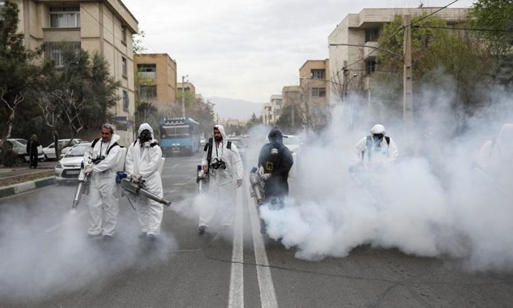 Lính cứu hỏa mặc đồ bảo hộ phun khử trùng đường phố ở thủ đô Tehran của Iran hôm 20/3. Ảnh: Reuters.