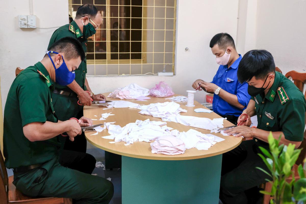 Biên phòng và đoàn thanh niên may khẩu trang để phát miễn phí cho dân, tại UBND phường Thanh Bình (quận Hải Châu) ngày 25/3. Ảnh: Nguyễn Đông.