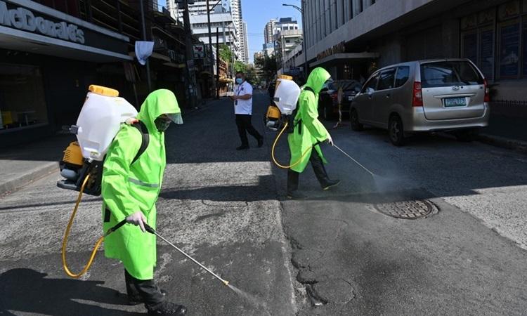 Công nhân mặc đồ bảo hộ phun khử trùng đường phố thủ đô Manila, Philippines hôm 19/3. Ảnh: AFP.