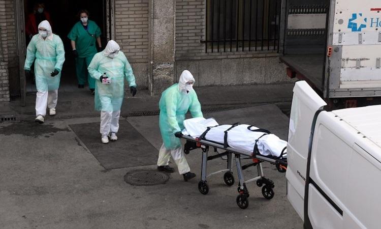 Nhân viên y tế Tây Ban Nha di chuyển thi thể một bệnh nhân Covid-19 tại bệnh viện ở Madrid hôm 25/3. Ảnh: AFP.