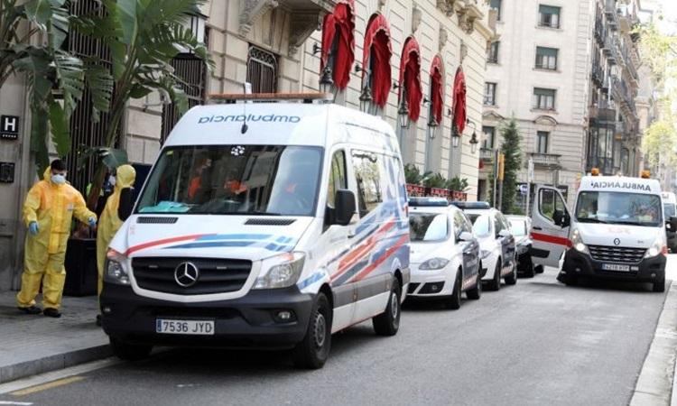 Xe cứu thương và nhân viên y tế chuẩn bị đón những bệnh nhân Covid-19 có triệu chứng nhẹ bên ngoài khách sạn ởBarcelona đầu tuần này. Ảnh: Reuters.