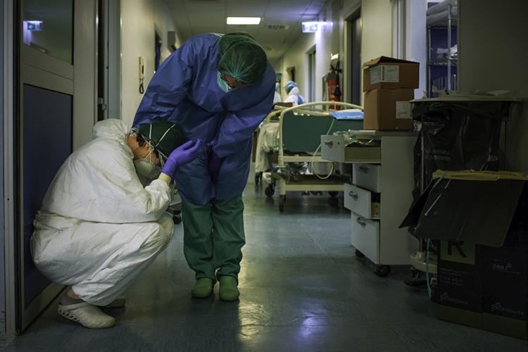 Một y tá động viên đồng nghiệp khi họ thay ca hôm 13/3 tại bệnh viện Cremona, thành phố Milan. Ảnh: AFP