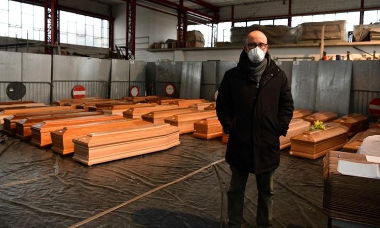 Người đứng đầu xãPonte San Pietro ở vùng Lombardy, Italy đứng trong nhà kho lưu trữ quan tài người chết vì Covid-119 hôm 26/3. Ảnh: AFP.
