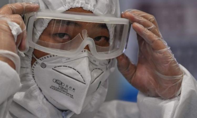 Nhân viên an ninh tại sân bay quốc tế Phố Đông Thượng Hải mặc đồ bảo hộ giám sát hành khách hôm 26/3. Ảnh: AFP.