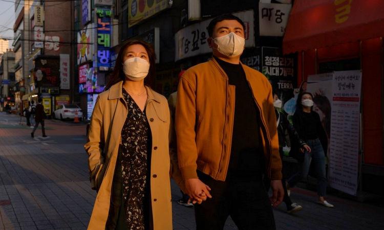 Người dân Hàn Quốc trên đường phố Seoul hôm 24/3. Ảnh: AFP.